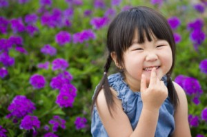 Child Smiling and Touching Her Mouth
