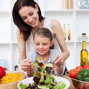 Parent Teaching Child How to Make Salad
