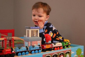 Child Playing with Toy Trains