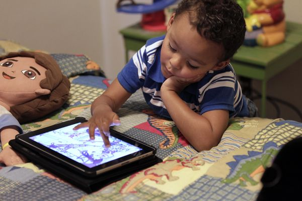 Boy plays with iPad