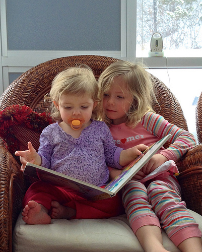 Older sibling reading to younger sibling