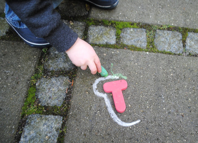 tracing letters in sidewalk chalk