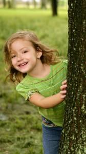 Girl playing behind tree