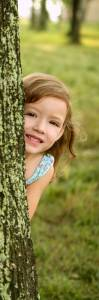 Girl Playing behind a tree